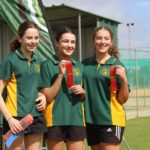 3 students from Mukinbudin District High School standing on podium with athletics carnival ribbons